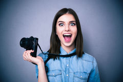 Amazed young pretty woman holding camera Stock Photo