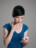 Amazed young short hair woman looking at cellphone. Amazed young short hair woman reading news on smart phone Stock Images