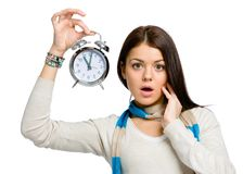 Amazed young woman with alarm clock Royalty Free Stock Photos