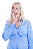Amazed young woman with blond hair and a blue blouse is shocked Royalty Free Stock Photos