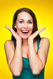 Amazed young woman. Casual young woman over yellow background Royalty Free Stock Images