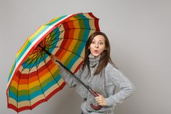 Amazed young woman in gray sweater, scarf holding colorful umbrella isolated on grey background in studio. Healthy royalty free stock photo