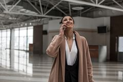 Amazed young woman is having mobile conversation in airport lounge. In touch. Excited charming lady is standing inside station building while looking up with Royalty Free Stock Image