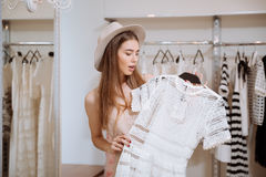 Amazed young woman holding and choosing dress in fashion boutique Royalty Free Stock Images