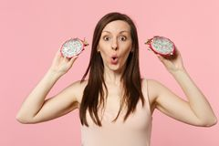 Amazed young woman holding in hands two halfs of fresh ripe pitahaya, dragon fruit isolated on pink pastel wall. Background in studio. People vivid lifestyle stock image