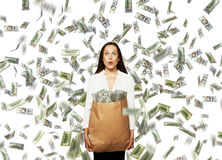 Amazed young woman holding money. Amazed young businesswoman holding paper bag with money under dollar's rain Stock Photos