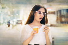 Amazed Young Woman Looking at Her Phone. Shocked woman looking at her phone holding a cup of coffee out in the city stock image
