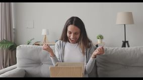 Amazed young woman opening cardboard box with internet store order.