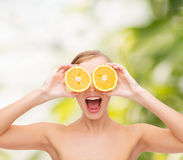 Amazed young woman with orange slices Stock Photo