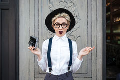 Amazed young woman photographer standing and holding photo camera. Amazed young woman photographer in black hat standing and holding photo camera Royalty Free Stock Image