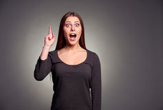 Amazed young woman pointing upward Royalty Free Stock Image