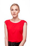 Amazed young woman. Portrait of the surprised girl in red dress over white background Royalty Free Stock Photo