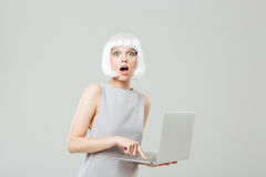 Amazed young woman pressing the button and using laptop Royalty Free Stock Images