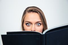 Amazed young woman reading book Royalty Free Stock Images