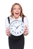 Amazed young woman showing the clock. Over white background Royalty Free Stock Image
