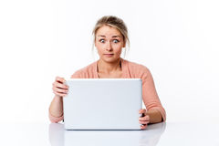 Amazed young woman sitting at clean desk staring at computer Royalty Free Stock Photography