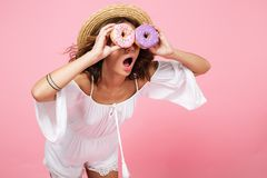 Amazed young woman in straw hat having fun and looking through d. Onuts, over pink background Stock Photos