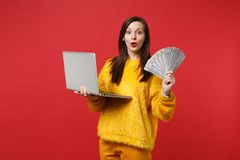Amazed young woman in yellow fur sweater holding laptop pc computer, fan of money in dollar banknotes, cash money. Isolated on red background. People emotions stock photos