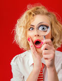 Amazedly funny woman. With magnifier, isolated on red background Royalty Free Stock Photo