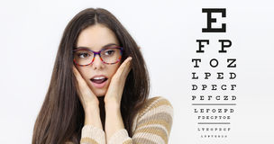 Amazement female face with spectacles on eyesight test chart Royalty Free Stock Photos