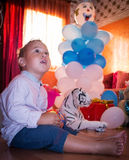 Amazement. Kid stood in admiration of birthday gifts royalty free stock photography