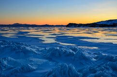 View of the ice and the rising sun over the mountains, lake Baikal royalty free stock image