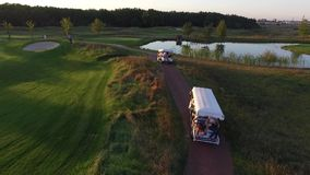 Amazing aerial footage of two golf carts on golf course at sunset stock video footage