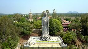 Aerial view giant Buddha statue among tropical park. Amazing aerial panorama giant Buddha grey statue among tropical park against pictorial landscape stock video