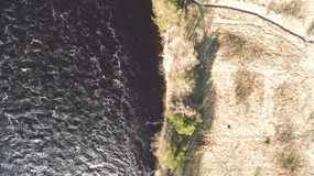 Amazing aerial shot of beautiful dark river shore. Forest background stock photography