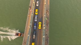 Amazing aerial shot of car traffic in a city bridge. Car traffic on a city bridge of Budapest from above. A little boat passing under the bridge stock video