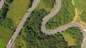 Amazing aerial shot of car traffic on forest serpentine road. Road through forest from above. Aerial shot of a green forest serpentine road with car traffic stock footage
