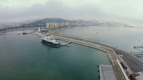 Stunning city of Malaga, aerial shot from near the shore, huge ship parked in the dock. Amazing aerial shot of dock area and Malaga city in the distance, massive stock footage