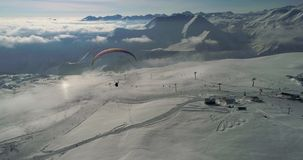 Amazing aerial video of paraplane at snow mountains. Close-up drone of paraglide winter`s mountains stock video footage