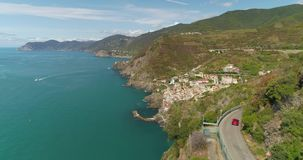 Mountain Road Aerial View. Amazing aerial view of beautiful Mediterranean landscape with curvy mountain road in the coastal seaside town. Top view of road to stock footage