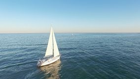 Aerial view of sail yacht sailing at sea near coastline. Blue sea with sun reflections. Drone view - birds eye angle.