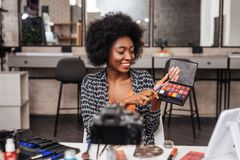 Amazing african american woman with curly hair working in a fashion studio. Fashion academy. Amazing african american woman with curly hair looking amused while royalty free stock photography