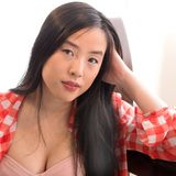 Lovely asian model in checkered shirt poses glamorously. Amazing Asian woman rests her arm on a bench and faces the camera in a low cut top stock image