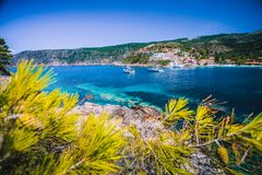 Amazing Assos village, Kefalonia. Greece. White cruise yachts staying at anchor in beautiful emerald green colored. Lagoon water. Framed by pine trees branches stock image