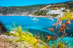 Amazing Assos village, Kefalonia. Greece. White cruise yachts staying at anchor in beautiful emerald green colored. Lagoon water. Framed by pine trees branches royalty free stock image