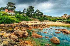 Amazing Atlantic ocean coast with granite stones,Perros-Guirec,France. Stunning rocky beach with pink granite stones and wonderful green gardens on the coast Stock Photography