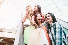 Amazing and attractive ladies are standing on escalator. They are looking to the left. They are smiling. Also teenagers. Look very excited stock photos