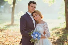 Amazing attractive young couple in wedding day. bride in elegant white long dress and blue bouquet in hand, the groom in. A blue fashionable business suit royalty free stock photos