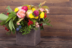 Amazing autumn bouquet with berries in a wooden vase Royalty Free Stock Photo