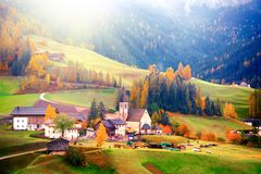 Colorful autumn scenery in Santa Maddalena village at sunrise. Dolomite Alps, South Tyrol, Italy. Amazing autumn scenery in Santa Maddalena village with church stock photo