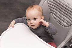 Amazing baby boy in baby chair looking at camera. Cute infant thoughtful kid. Royalty Free Stock Images