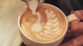 Amazing barista tutorial of making art latte, shape of a swan. Female hands, portrait. Inside shooting. Cafe business
