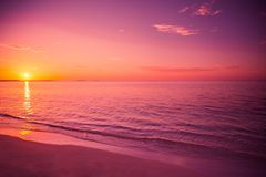 Amazing beach sunset. Relaxing colors with soft waves royalty free stock images