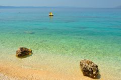 Amazing beach with two big stones and crystal clear water Royalty Free Stock Image