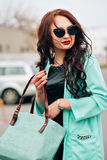 Amazing beautiful girl with dark hair. Fashion handbag, long coat mint color. Stylish sunglasses. Red plump lips Stock Photo