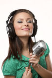 Amazing beautiful girl with studio microphone. Amazing beautiful girl with professional studio microphone and headphones on white background in studio shooting royalty free stock photos